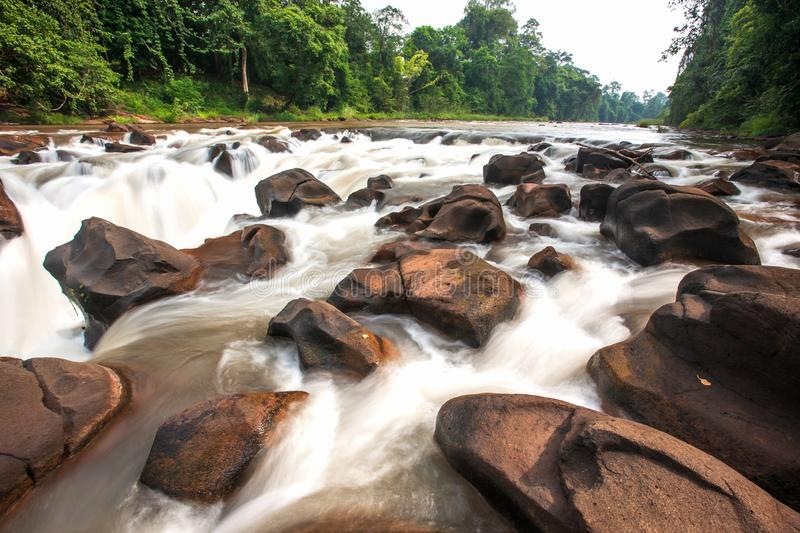 Pure nature water. Tad Pha Suam waterfall in winter season. Beautiful rocks and gently waters falling off the cliff in tropical. Forest. Bolaven Plateau, Pakse stock image