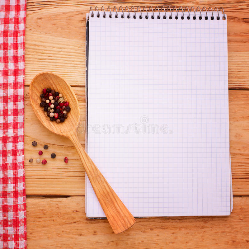 Pure notebook for recording menu, recipe on red checkered tablecloth tartan. Wooden table close up view from top stock images