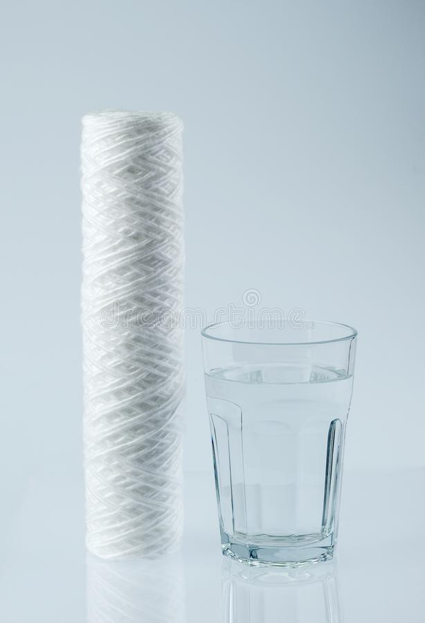 Pure water in glass and water filter.Water and water filter. New water filter cartridge and a glass of clean drinking water on the table . New  filter for royalty free stock photo