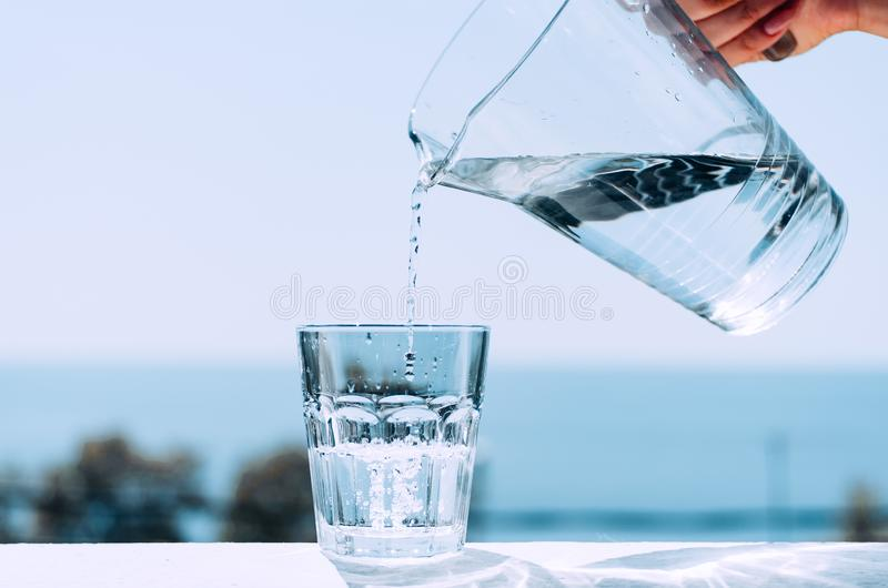 Pure water from a jug is poured into a glass beaker. Glass with water on the background of the sea royalty free stock images