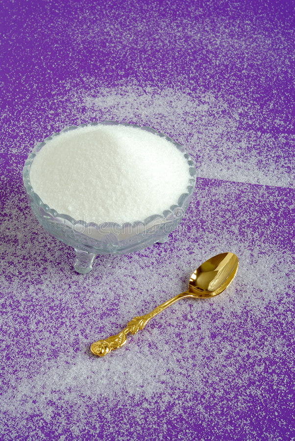 Pure White Granulated Sugar on a Purple Background royalty free stock photography