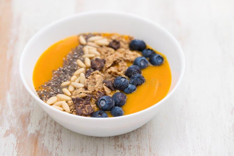 Puree van mango met granola, chia en bessen in witte kom stock afbeeldingen