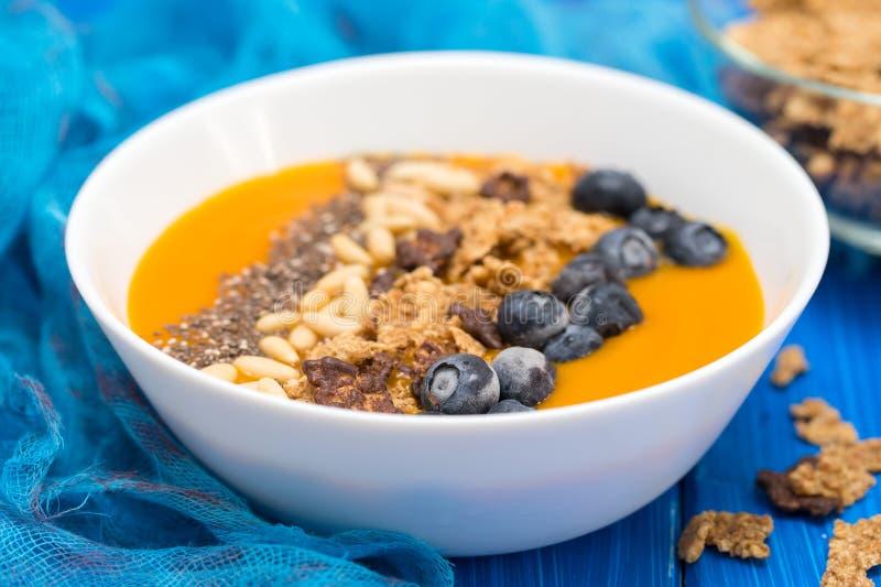 Puree van mango met granola, chia en bessen in witte kom royalty-vrije stock afbeeldingen