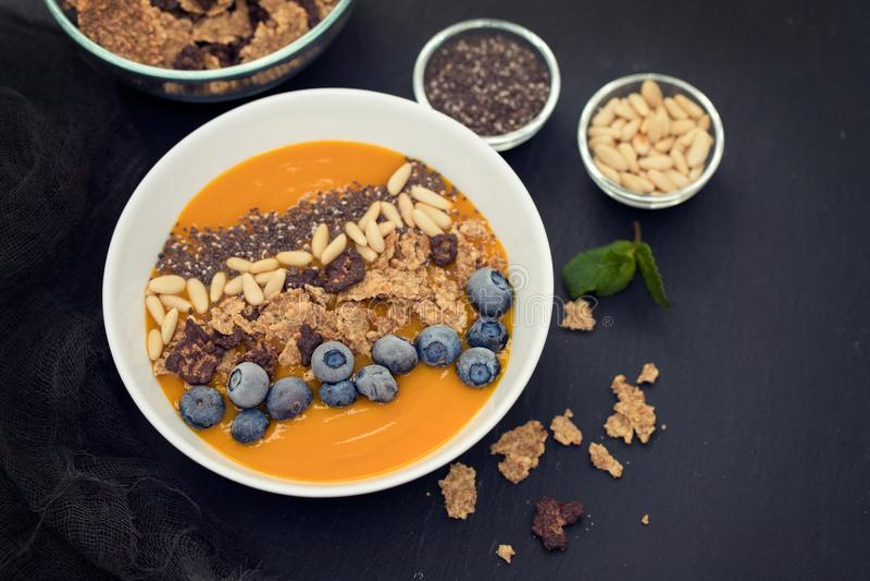 Puree van mango met granola, chia en bessen in witte kom royalty-vrije stock fotografie