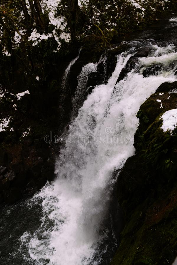 A purely white small waterfall streaming down royalty free stock photos