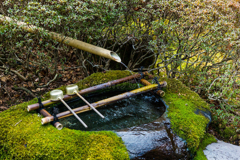 Purificación del agua en la entrada del templo japonés Cucharón de Japón en capilla imágenes de archivo libres de regalías