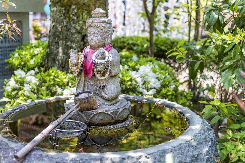 Purification fountain in Daisho-in temple in Itsukushima island, Japan. Itsukushima, Japan - April 27, 2014: A purification fountain in Daisho-in temple. At the stock photo