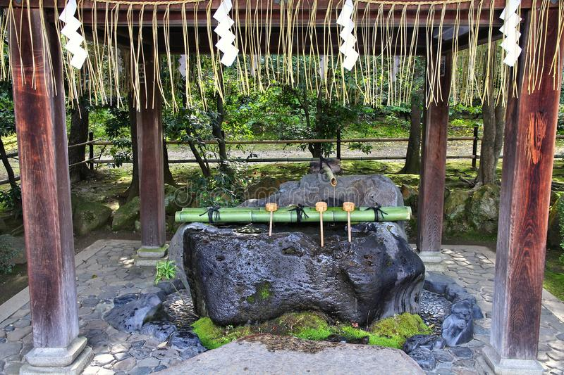Purification fountain. Japan culture - purification fountain with wooden ladles at a Buddhist temple (Ryoanji) in Kyoto royalty free stock images