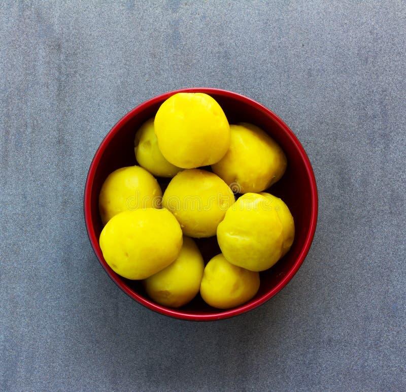 Purified ferveu batatas amarelas em uma bacia vermelha em um fundo cinzento imagem de stock royalty free