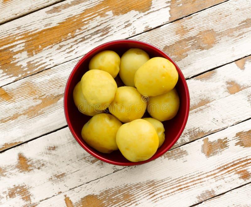 Purified ferveu batatas amarelas em uma bacia vermelha na tabela de madeira velha com os restos do close up branco da pintura fotos de stock royalty free