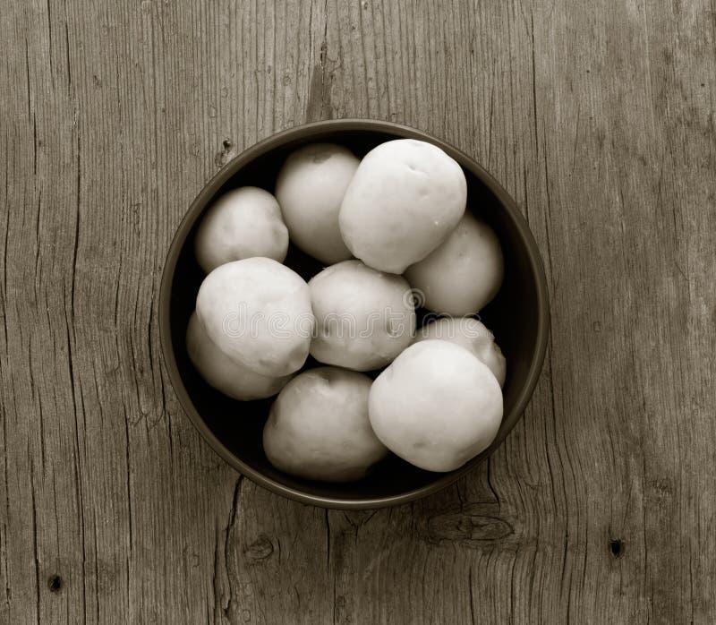 Purified ferveu batatas em uma placa circular em uma tabela de madeira velha com close up das quebras fotos de stock