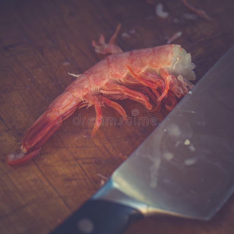 Purified ferveu o camarão e uma mentira da faca de cozinha em uma placa de corte Imagem tonificada imagens de stock