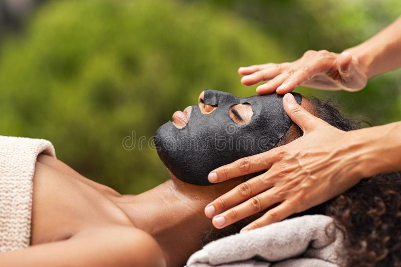 Purifying black beauty mask on woman face. Hands of masseuse applying black charcoal mask on african women face. Young women getting black mask face massage in stock photography