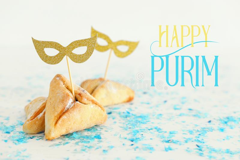 Purim celebration concept & x28;jewish carnival holiday& x29;. Traditional hamantaschen cookies with cute gold masks. Over white wooden table stock image