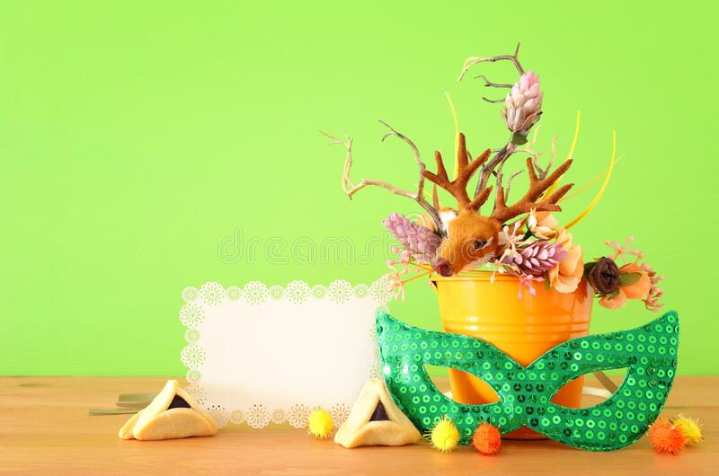 Purim celebration image jewish carnival holiday with traditional hamantasch cookies and deer antlers floral decoration over stock image