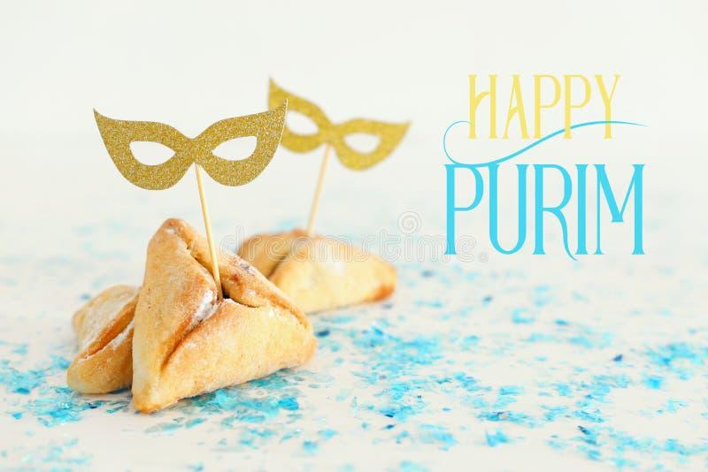 Purim-Feierkonzept u. x28; jüdisches Karneval holiday& x29; Traditionell hamantaschen Plätzchen mit netten Goldmasken stockbild
