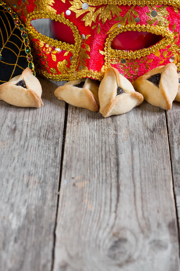 Purim. Hamantaschen cookies or Haman's ears and carnival masks for Purim celebration (jewish holiday). Copy space background stock photography