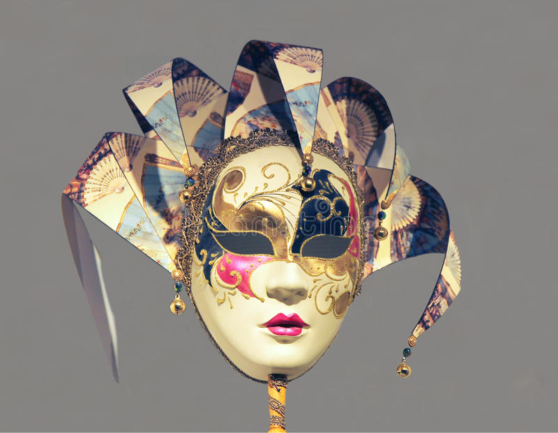 Purim mask. Painted with colorful colors on gray background royalty free stock images
