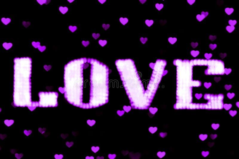 Purpúreo claro de neón púrpura borroso de la muestra LED Bokeh del AMOR del texto en bokeh del fondo enciende el corazón suavemen foto de archivo