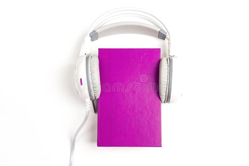 Purper boek met witte hoofdtelefoons op het op witte achtergrond royalty-vrije stock afbeelding