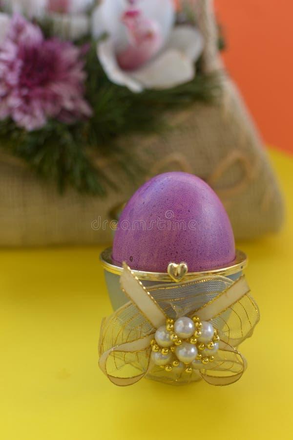 Purper ei in doos met gouden lint en parel stock afbeelding