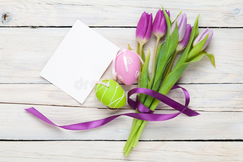 Purper tulpenboeket, paaseieren en lege groetkaart stock foto's
