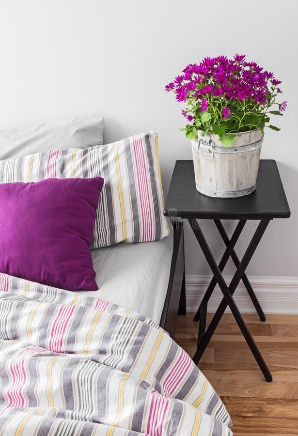 Purpere bloemen in een heldere slaapkamer stock afbeelding