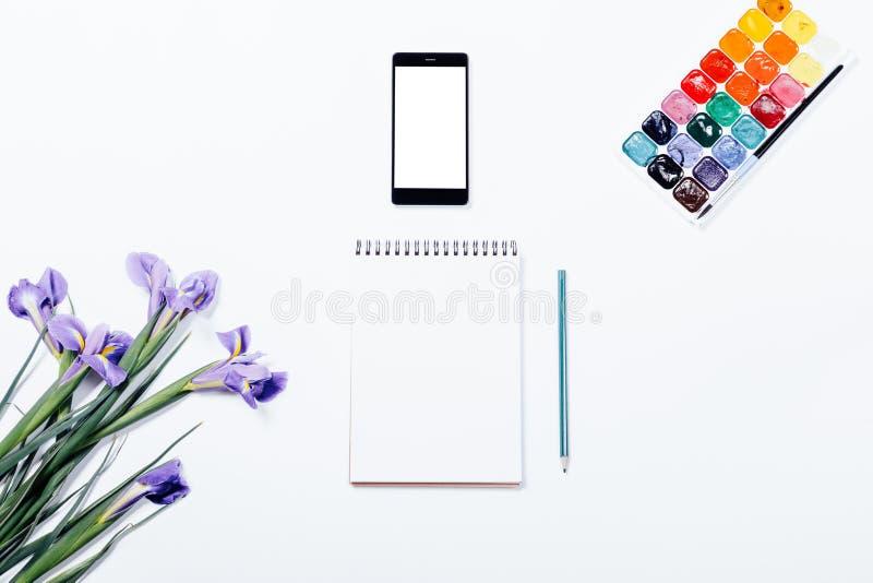 Purpere bloemen, mobiele telefoon, notitieboekje, potlood en waterverfpa stock afbeeldingen