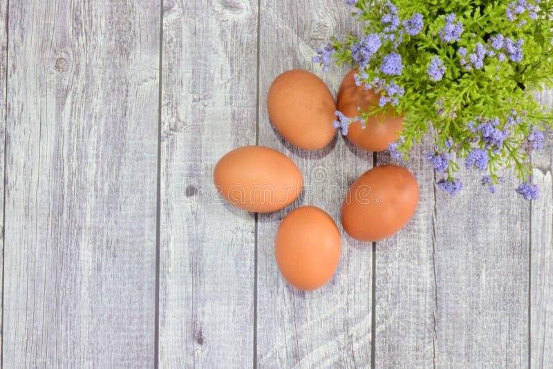 Purpere bloemvaas en 5 eieren op grijze houten vloer stock afbeeldingen