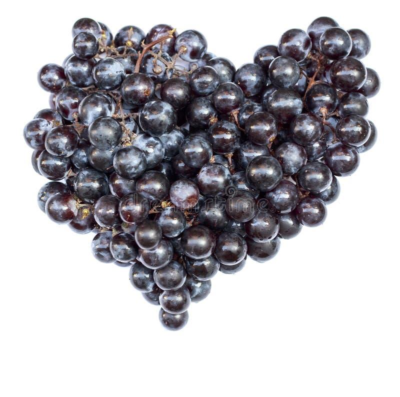 Purpere die druiven in de vorm van hartclose-up op witte achtergrond wordt geïsoleerd stock foto's