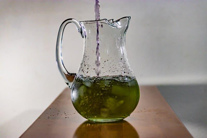 Purpere die vloeistof in groene waterkruik wordt gegoten royalty-vrije stock foto's