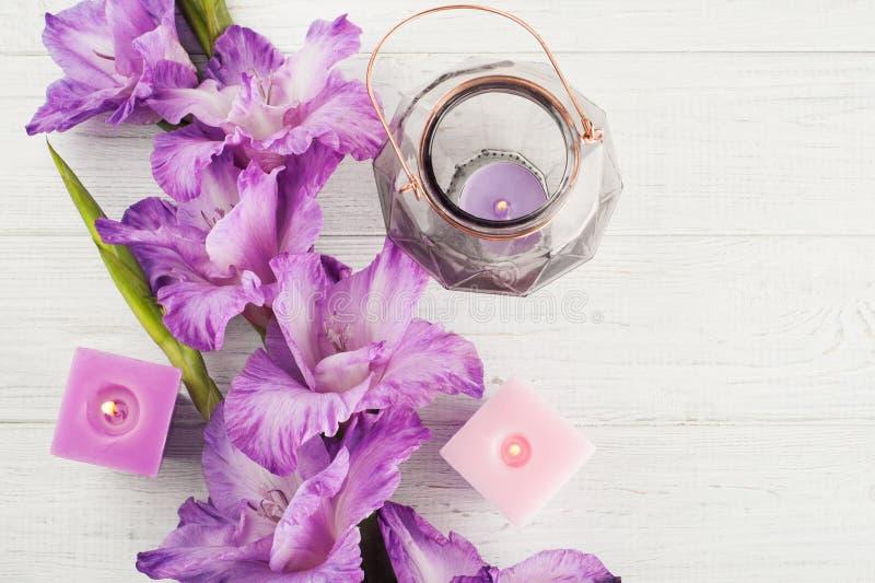 Purpere gladiolen en aangestoken kaarsen op witte lijst royalty-vrije stock afbeeldingen