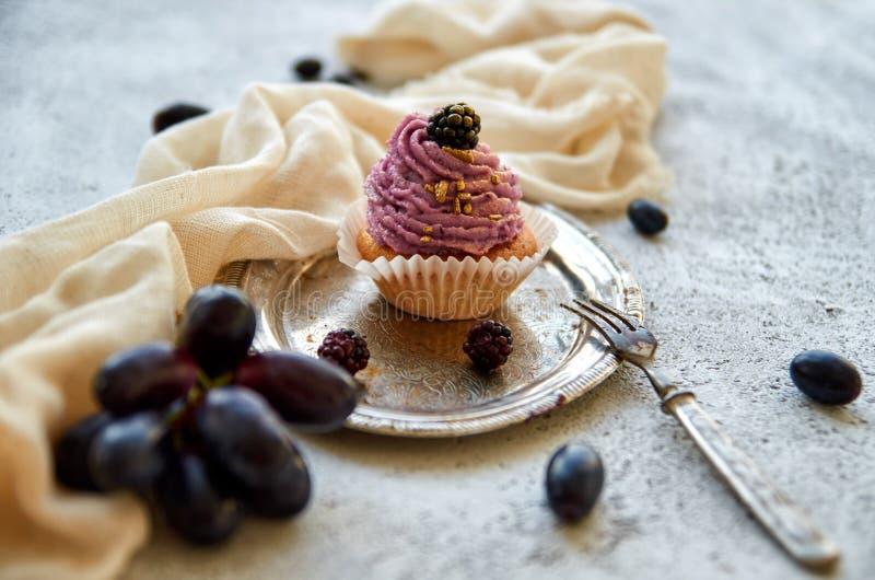 Purpere gouden cupcake met braambes op uitstekend die dienblad met vork, lichte doek, verse blauwe druiven en braambessen wordt v stock afbeeldingen