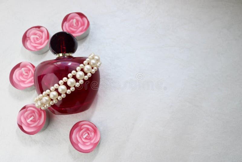 Purpere mooie glas transparante fles vrouwelijk die parfum met witte kleurloze parels en roze paraffinekaarsen wordt verfraaid in stock foto's