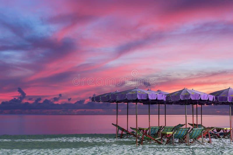 Purpere paraplu en groene stoelen in ochtendstrand, zonsopgangschot royalty-vrije stock afbeelding