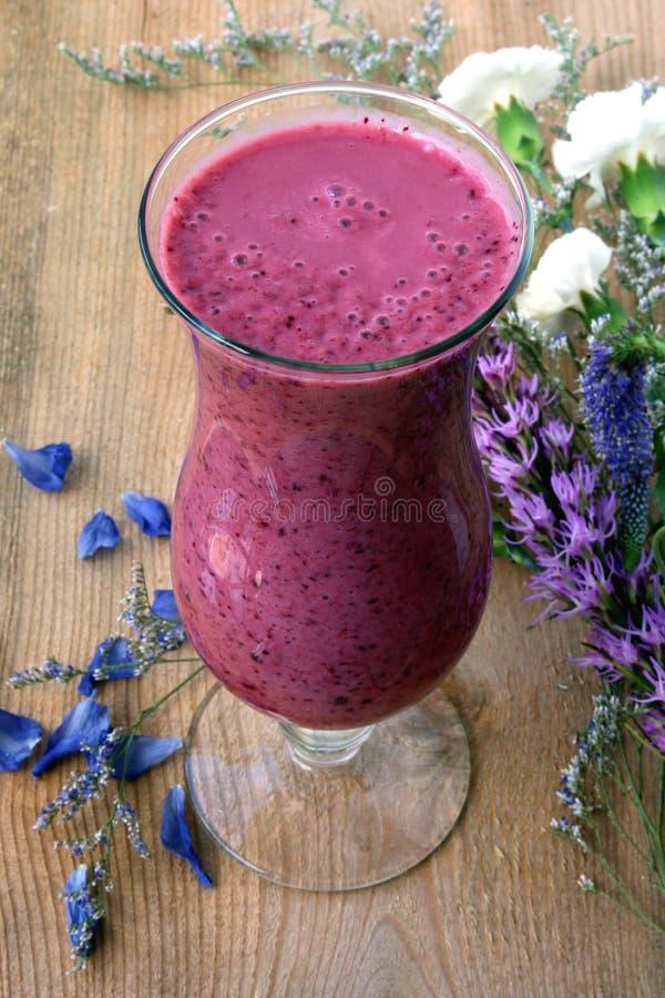 Purpere smoothie met blauwe en witte bloem stock foto