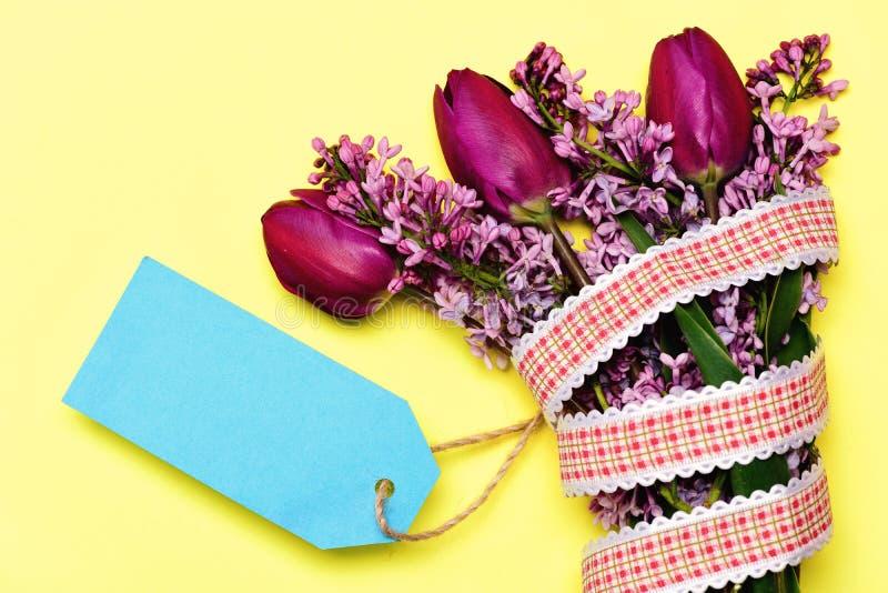 Purpere tulpen en lilac bloemen en cyaan blauwe kaart royalty-vrije stock afbeelding