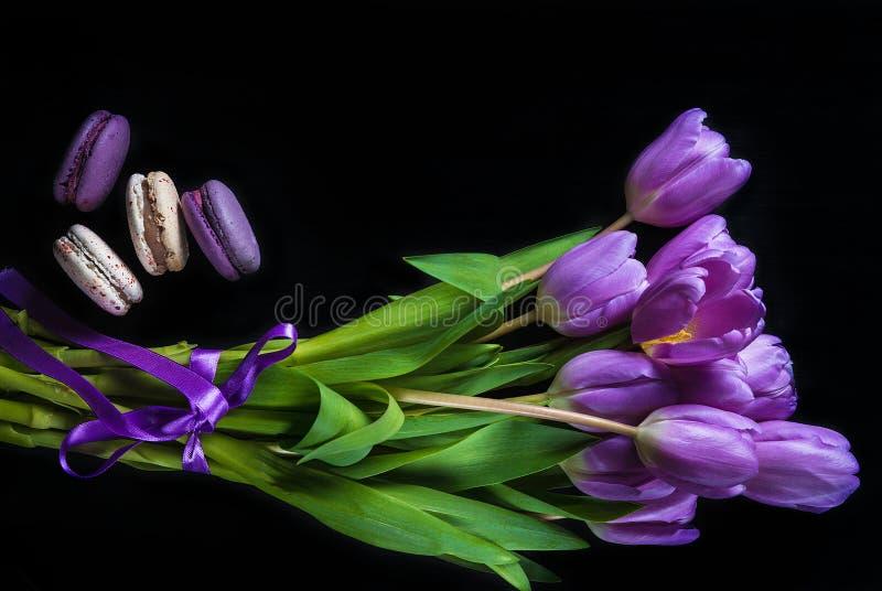 Purpere tulpen en macaronikoekjes op een zwarte achtergrond royalty-vrije stock foto's