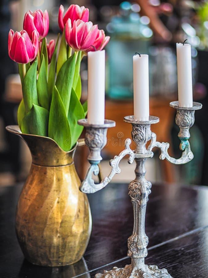 Purpere tulpen in metaalvaas met kaarsen op houten achtergrond stock afbeelding