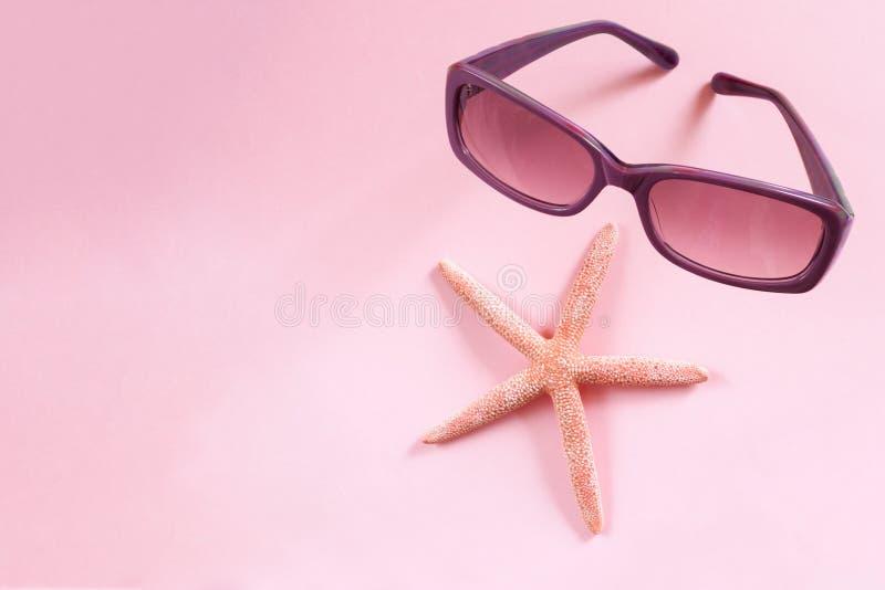 Purpere zonnebril en zeester op roze achtergrond stock foto's