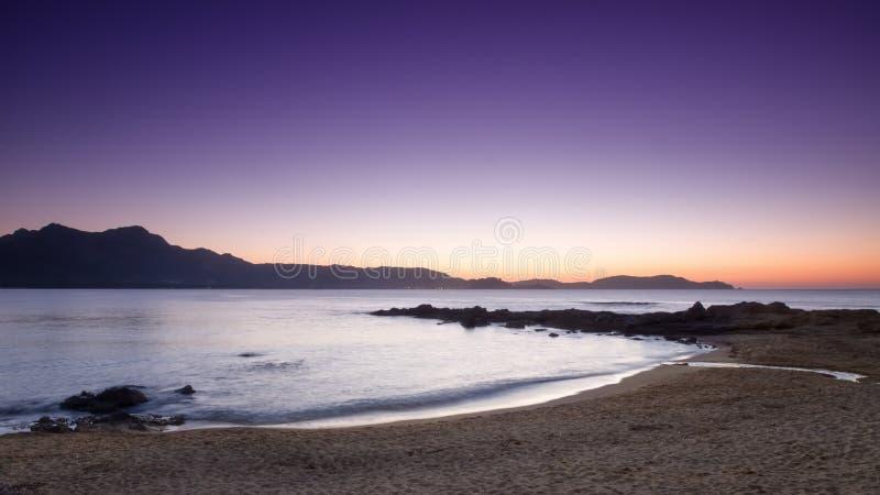 Purpere zonsondergang bij Arinella-strand in Corsica stock afbeelding
