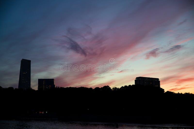 Purpere zonsondergang tegen de achtergrond van silhouetten van huizen met meerdere verdiepingen stock foto