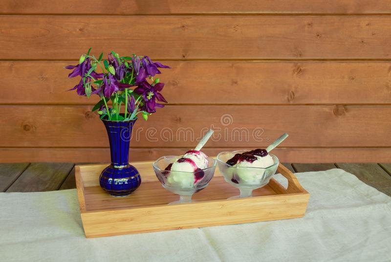 Purple aquilegia wildflowers and sundae ice cream with blueberry syrup on aged wooden table royalty free stock photography