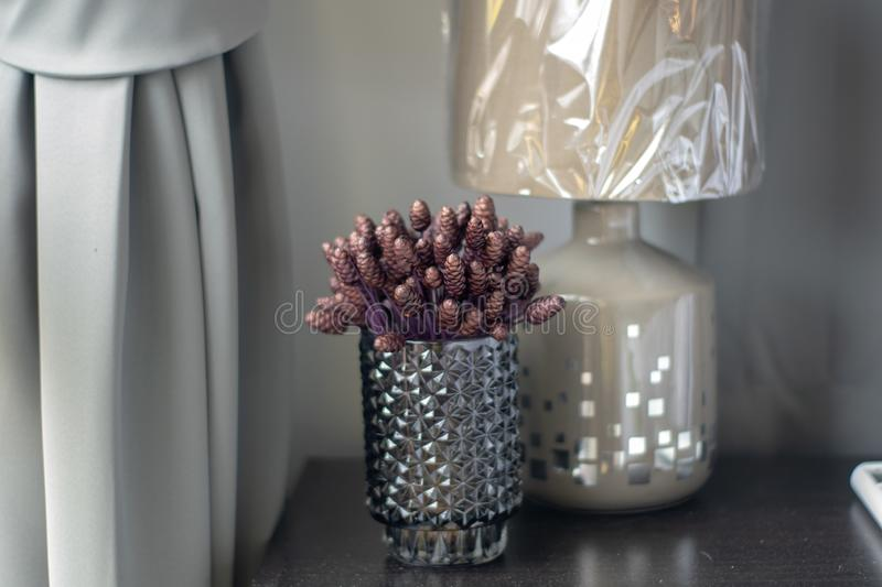 Purple artificial flowers in clear crystal glass royalty free stock photo
