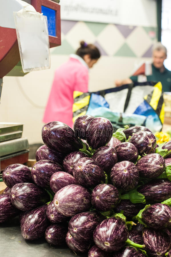 Purple aubergines heap in market royalty free stock images