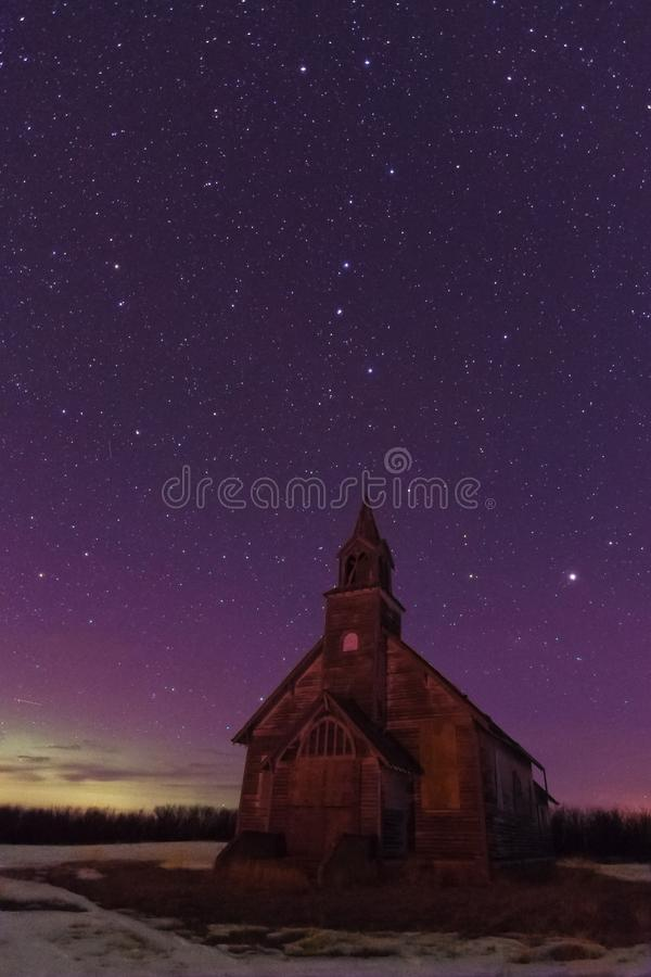Purple Aurora Sky over Abandoned Saskatchewan Church in the Winter. A purple aurora sky and stars over an abandoned church near Stewart Valley in southwest stock images