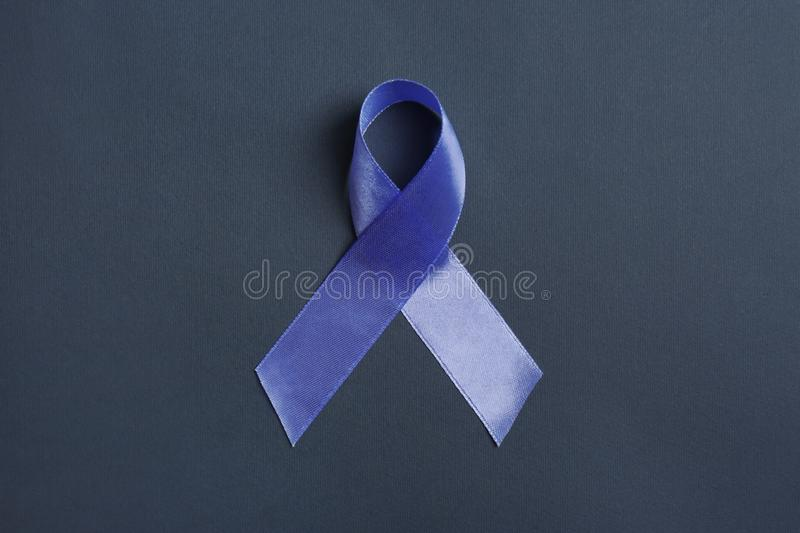 Purple awareness ribbon on black background. Top view stock images