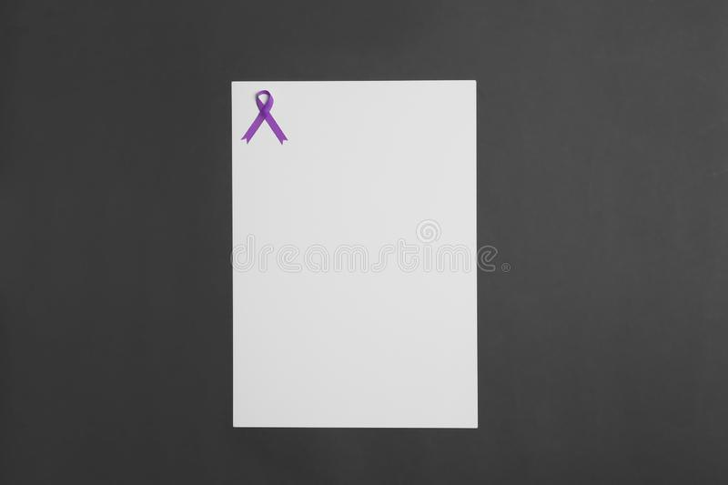 Purple awareness ribbon and blank card on black background, top view. With space for text royalty free stock image