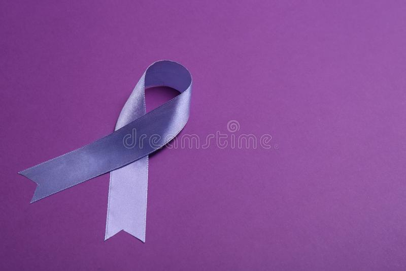 Purple awareness ribbon on color background. Space for text royalty free stock photos