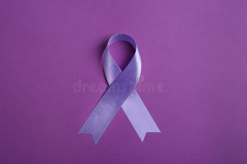 Purple awareness ribbon on color background. Top view stock photos